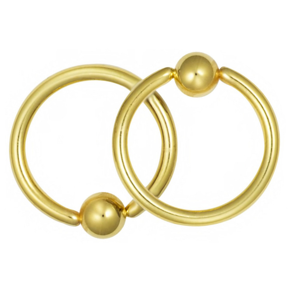"""These 16 gauge 7/16"""" captive bead rings are made with surgical grade 316L Stainless Steel and yellow gold IP plating. IP (Ion Plating) is a safe and permanent fusion coating process used to enhance the durability, color and shine of body jewelry. These hoops can be worn in virtually any 16 gauge piercing and are most commonly used for the septum, lip and various piercings on the ear. These hoops come with 4 mm balls and they are hypoallergenic and nickel free."""